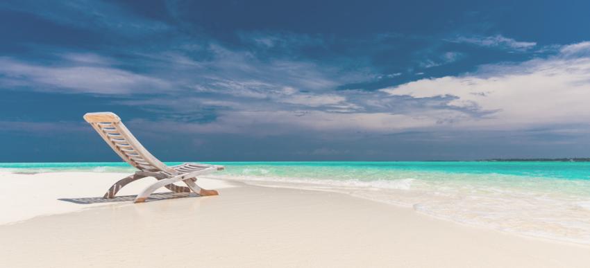sun lounger on an empty white sandy beach with blue sky and blue sea