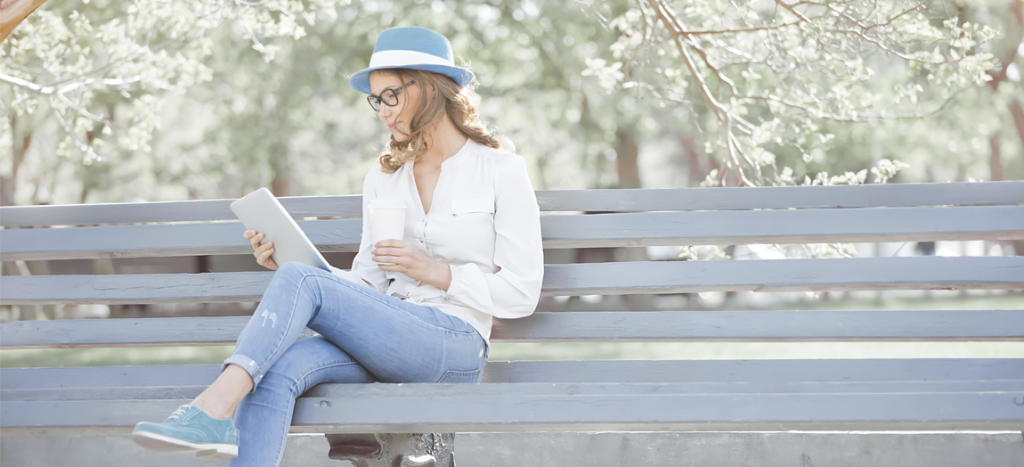 Woman reading a kindle on a bench