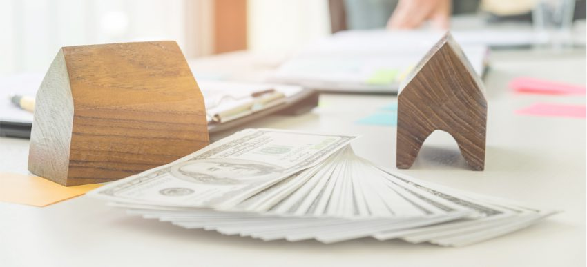wooden houses on desk with American money spread on the table between them. Things To Consider Before Investing In Real Estate