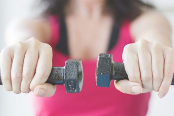woman doing exercise - dumbbells in hands.